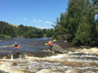 2 young men in kayaks on river